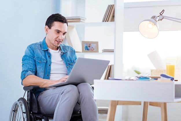 Zuhause arbeiten. gelähmte männliche person, die laptop auf knien hält und lächeln auf gesicht hält, während sie bildschirm betrachtet