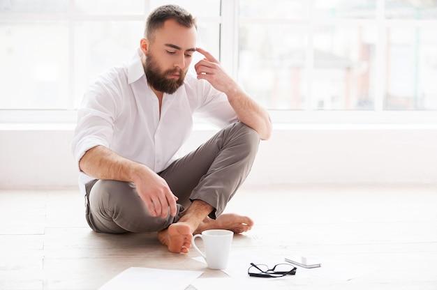 Zuhause arbeiten. selbstbewusster junger mann, der den kopf mit dem finger berührt und die dokumente betrachtet, während er in seiner wohnung auf dem boden sitzt