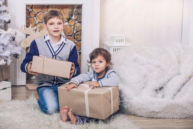Zuhause einen glücklichen jungen und ein mädchen mit geschenkboxen im weihnachtsinterieur