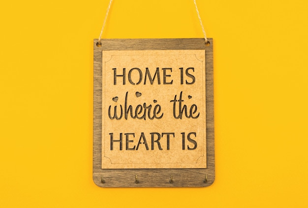 Zuhause ist, wo das herz ist, holzplatte für schlüssel, gemütliches und süßes heimdekorationskonzept, gelbes hintergrundfoto