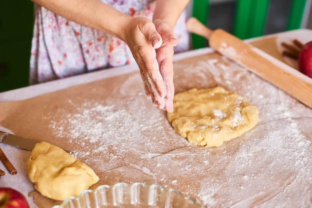 Zuhause kochen. hände arbeiten mit teigzubereitungsrezeptbrot. weibliche hände, die teig für pizza machen. frauenhände rollen den teig. mutter rollt teig auf dem küchenbrett mit einem nudelholz