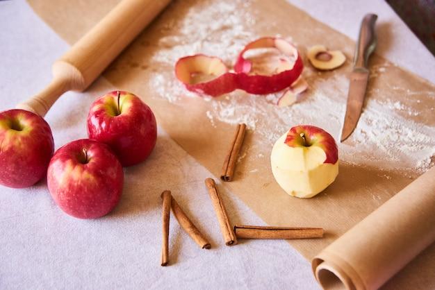 Zuhause kochen. reifer geschälter apfel. backzutaten auf den tisch gelegt, fertig zum kochen. konzept der lebensmittelzubereitung, weiße tabelle auf hintergrund