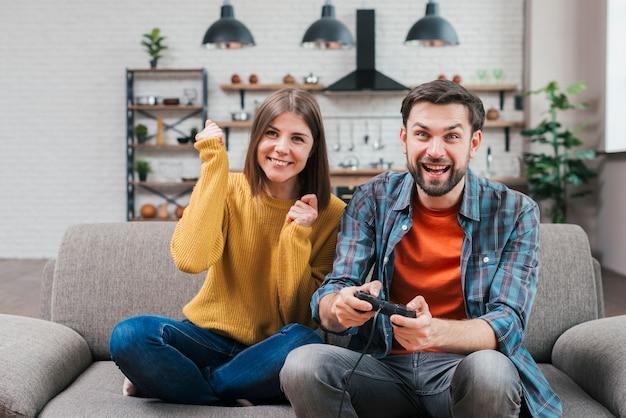 Zujubelnde junge paare, die auf dem sofa spielt das videospiel sitzen