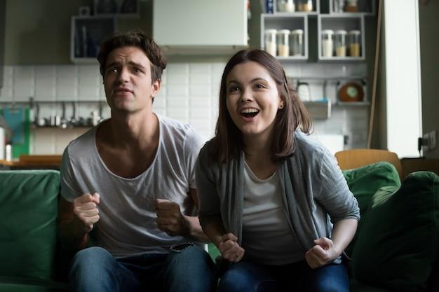 Zujubelndes unterstützendes gewinnendes team der paare, das zu hause fernsehspiel überwacht