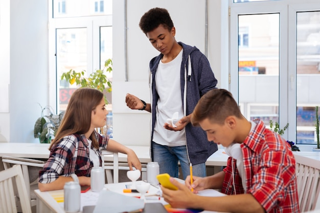 Zukünftige möbel. junge vielversprechende innenarchitekten, die über zukünftige möbel sprechen, die kleines stuhlmodell halten