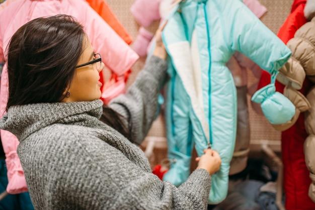 Zukünftige mutter im laden für neugeborene, stoffabteilung. schwangere frau im laden von waren für säuglinge