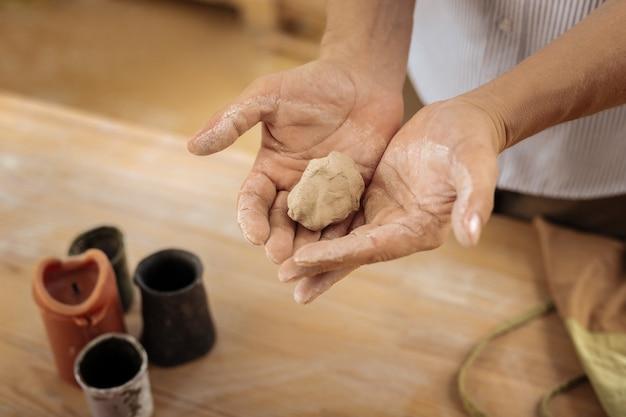 Zukünftige vase. kreativer erfahrener handwerker, der vorbereitungen für zukünftige vasen in seinen händen hält, während er hart arbeitet