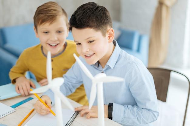 Zukünftiger architekt. angenehmer kleiner junge, der neben seinem bruder am arbeitsplatz seines vaters sitzt und lächelnd windturbinen in sein notizbuch zeichnet