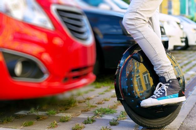 Zukunft ist jetzt konzept. ökologischer transport. schwarzes modernes futuristisches elektrisches einrad, einradroller oder ausgleichendes elektrisches rad im vergleich zu benzindieselautos. öko-planeten-konzept