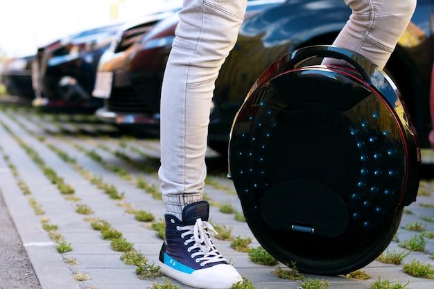 Zukunft ist jetzt konzept. ökologischer transport. schwarzes modernes futuristisches elektrisches einrad, einradroller oder ausgleichendes elektrisches rad vergleichen mit benzin benzin diesel gelb auto. öko-planeten-konzept