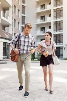 Zum büro. nettes junges paar, das flaschen smoothie hält, während sie zusammen zur arbeit gehen
