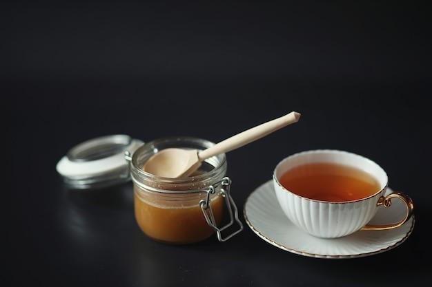 Zum frühstück stellen. süßigkeiten und gebäck mit nüssen für tee auf schwarzem hintergrund. eine kaffeetasse und pastetchen.