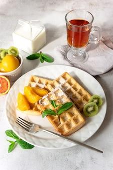 Zum frühstück werden frische belgische waffeln mit früchten serviert
