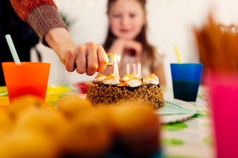 Zündung von Kerzen auf Geburtstagskuchen