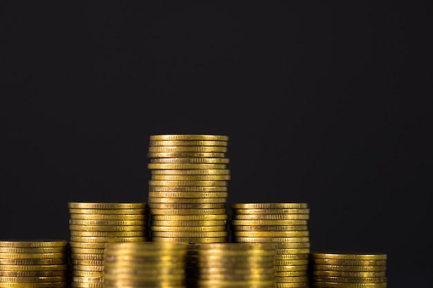 Zunehmende spalten von münzen, schritt von stapeln prägen auf dunklem hintergrund mit kopienraum für geschäft und finanzkonzept.