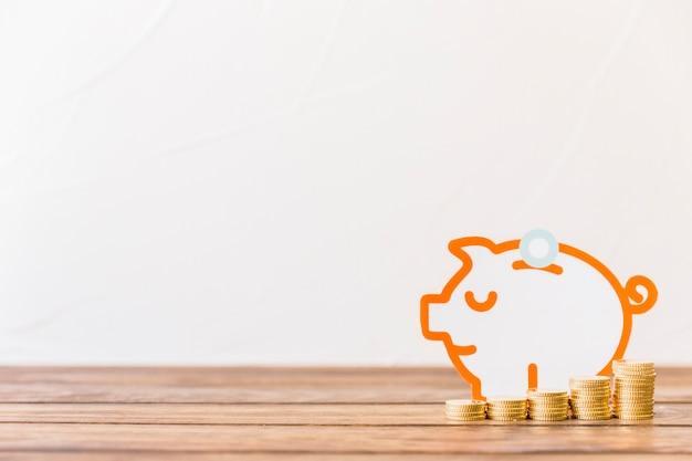 Zunehmende staplungsmünzen vor piggybank auf holzoberfläche