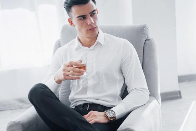 Zur seite schauen. nahaufnahme. junger eleganter kerl im weißen anzug sitzt auf dem stuhl und hält glas mit alkohol.
