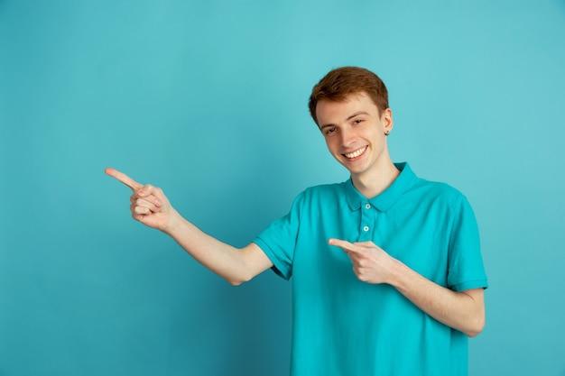 Zur seite zeigend. das moderne porträt des kaukasischen jungen mannes lokalisiert auf blauer wand, monochrom. schönes männliches model. konzept der menschlichen emotionen, gesichtsausdruck, verkauf, anzeige, trendy.