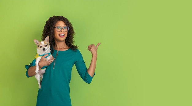 Zur seite zeigend. porträt der jungen frau des afroamerikaners lokalisiert auf grünem studiohintergrund. schönes weibliches modell mit kleinem hündchen. konzept der menschlichen emotionen, gesichtsausdruck, verkauf, anzeige.