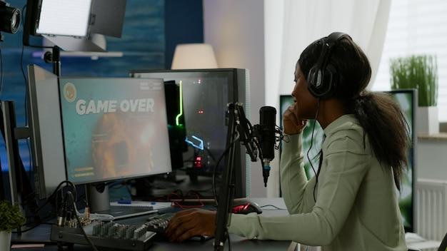Zurück aufnahme von afroamerikanischen esport-streaming, das den virtuellen wettbewerb mit kopfhörern verliert. professioneller gamer, der online-videospiele mit neuer grafik auf einem leistungsstarken computer streamt.