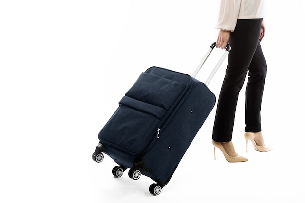 Zurück der geschäftsfrau, die in eine reise geht und gepäck auf weißem raum isoliert trägt