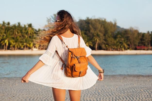 Zurück der schönen frau im weißen kleid, das sorglos am tropischen strand mit lederrucksack geht.