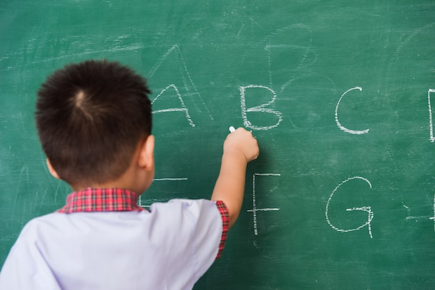 Zurück des asiatischen kleinen kinderjungenkindergartens in der studentenuniform, die abc mit kreide auf grüner tafel schreibt