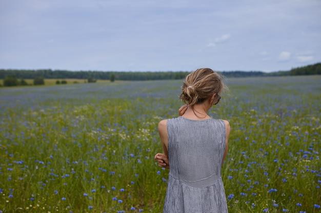 Zurück im freien porträt der zarten blonden jungen frau, die sommerkleid trägt, das erstaunliche wilde naturansicht während des straßenausfluges betrachtet, süßen frischen blumenduft atmet, sich friedlich und entspannt fühlt