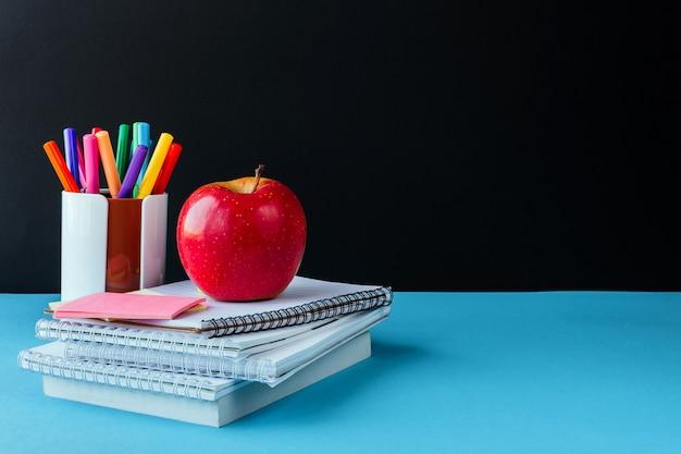 Zurück in der schule arbeit, arbeitsplatz eines schulkindbriefpapiers, notizbücher auf blau