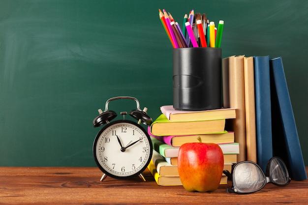 Zurück in die schule - apfel und bücher mit stiften und tafel