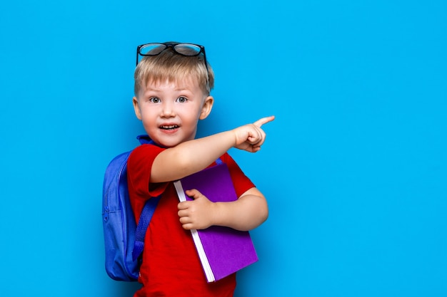 Zurück in die schule erste klasse junior lifestyle. kleiner junge im roten t-shirt. schließen sie herauf das studiofotoporträt des lächelnden jungen in den gläsern mit der schultasche und buch und mit seinem finger anzeigen