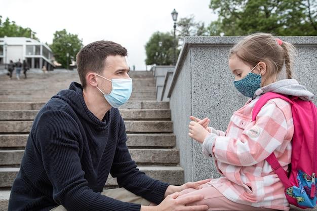 Zurück in die schule, pandemie. junger vater und kleine tochter in einer maske. freundliche familiäre beziehungen.
