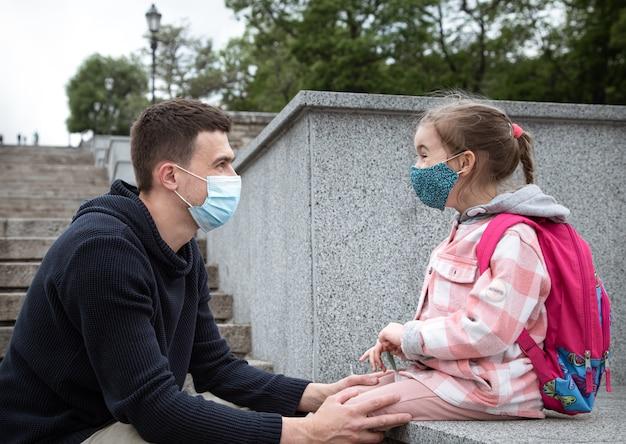 Zurück in die schule, pandemie. junger vater und kleine tochter in einer maske. vater händchen haltend mit seinem kind.