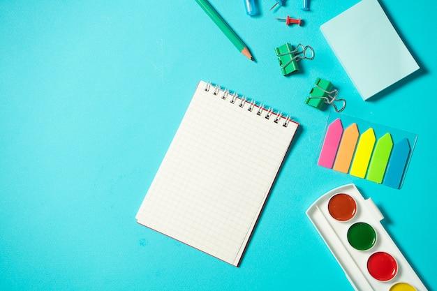 Zurück in die schule verspotten. flache komposition mit aquarell, bleistift, notizbuch, lineal, radiergummi. isometrisches konzept auf blauem hintergrund. pop-art. schulmaterial. overhead. branding mock-up-briefpapier