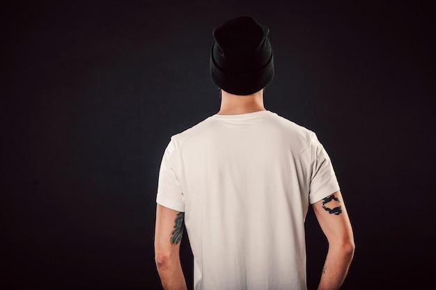 Zurück schuss des hübschen bärtigen mannes mit frischem haarschnitt und tätowierten armen, die auf lokalisiertem wandmodell im weißen einfachen leeren t-shirt bereit für entwürfe aufwerfen