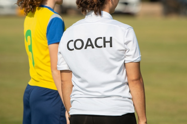 Zurück vom sporttrainer, der trainings-hemd an einem sportfeld im freien trägt