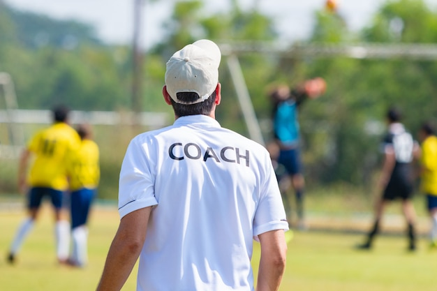 Zurück vom tragenden weißen trainer des fußballtrainers, der sein team während eines spiels trainiert