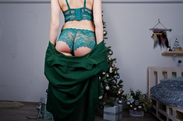 Zurück von arsch gesäß sexy blondes modell in grünen dessous gegen neujahr im reinraum.