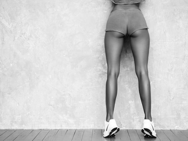 Zurück von der eignungsfrau in der sportkleidung, die überzeugt schaut junge weibliche tragende sportkleidung. schönes modell mit perfektem gebräuntem körper frau, die im studio nahe grauer wand aufwirft