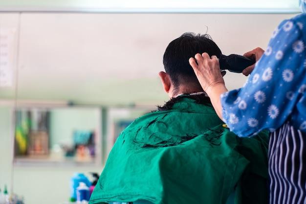 Zurück von einem mann, der haare im friseursalon schneidet