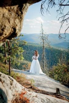 Zurück von mädchen im hochzeitskleid, das auf felsen in den bergen sitzt und zum fjord schaut, wandern in den hügeln
