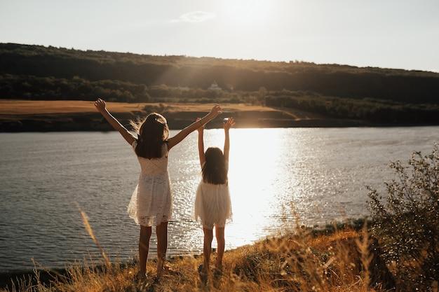Zurück von niedlichen zwei kindermädchen in weißen kleidern mit den händen hoch