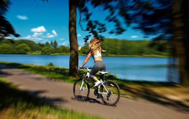 Zurück von sexy heißem sport blondes frauenmädchenmodell, das auf fahrrad im grünen sommerpark nahe see mit fliegendem erhöhtem haar in der luft reitet