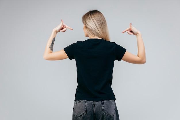 Zurück von stilvollem blondem mädchen, das schwarzes t-shirt posierend aufwirft