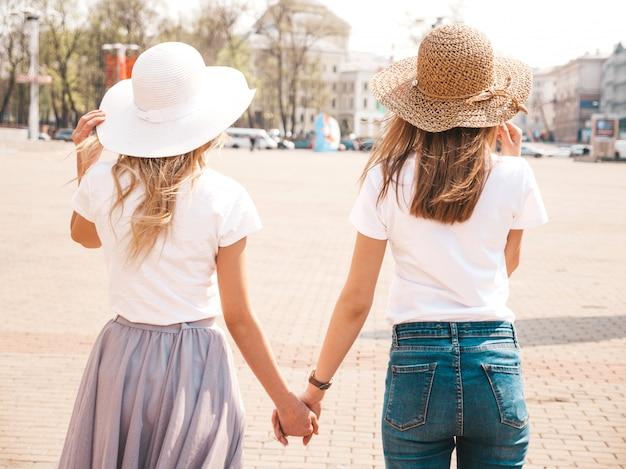 Zurück von zwei jungen schönen blonden lächelnden hippie-mädchen in der weißen t-shirt kleidung und im hut des modischen sommers. . paar einander die hände halten