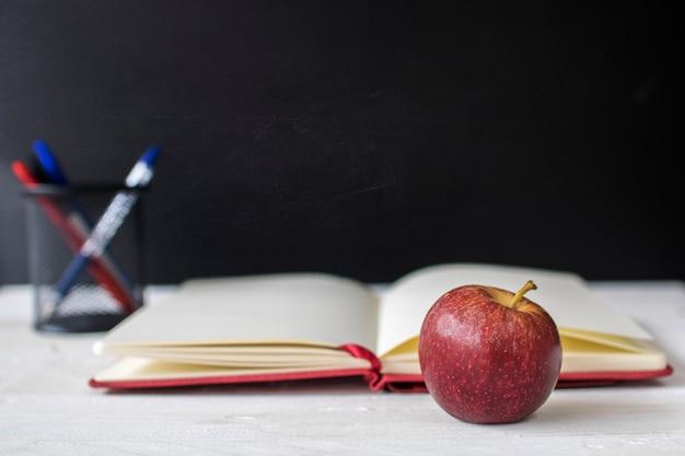 Zurück zu schul-, bildungs- und wissenskonzept, apfel und anmerkungsbuch auf tafelfronttafel