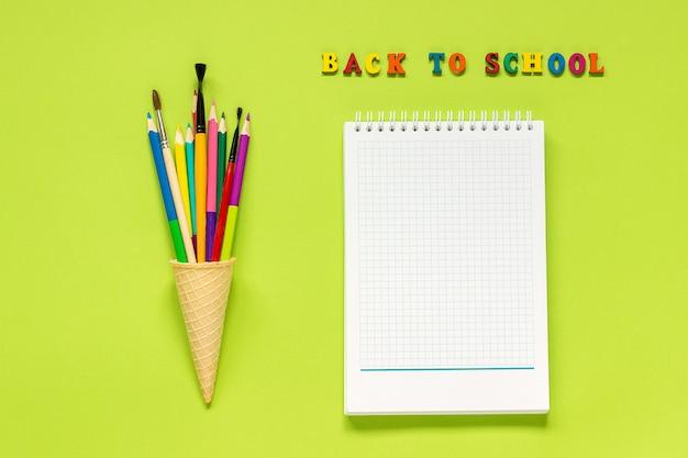 Zurück zu schule und farbigem bleistiftmalerpinsel in der waffeleiskegel und -notizbuch auf grünem hintergrund.