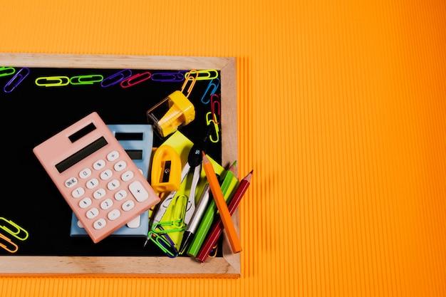 Zurück zu schulkonzept. bildungsausrüstung auf tafel auf orange hintergrund.