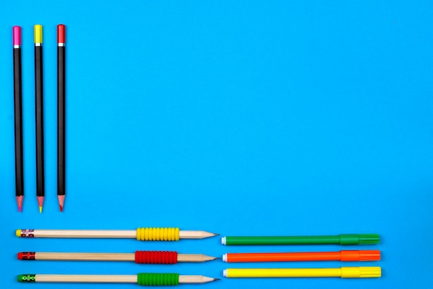 Zurück zu schulkonzept: feld mit farbigen bleistiften und zeichenstiften auf einem blauen hintergrund