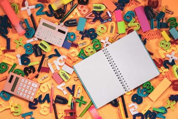 Zurück zu schulkonzept. notebook und bildung ausrüstung auf orange hintergrund.
